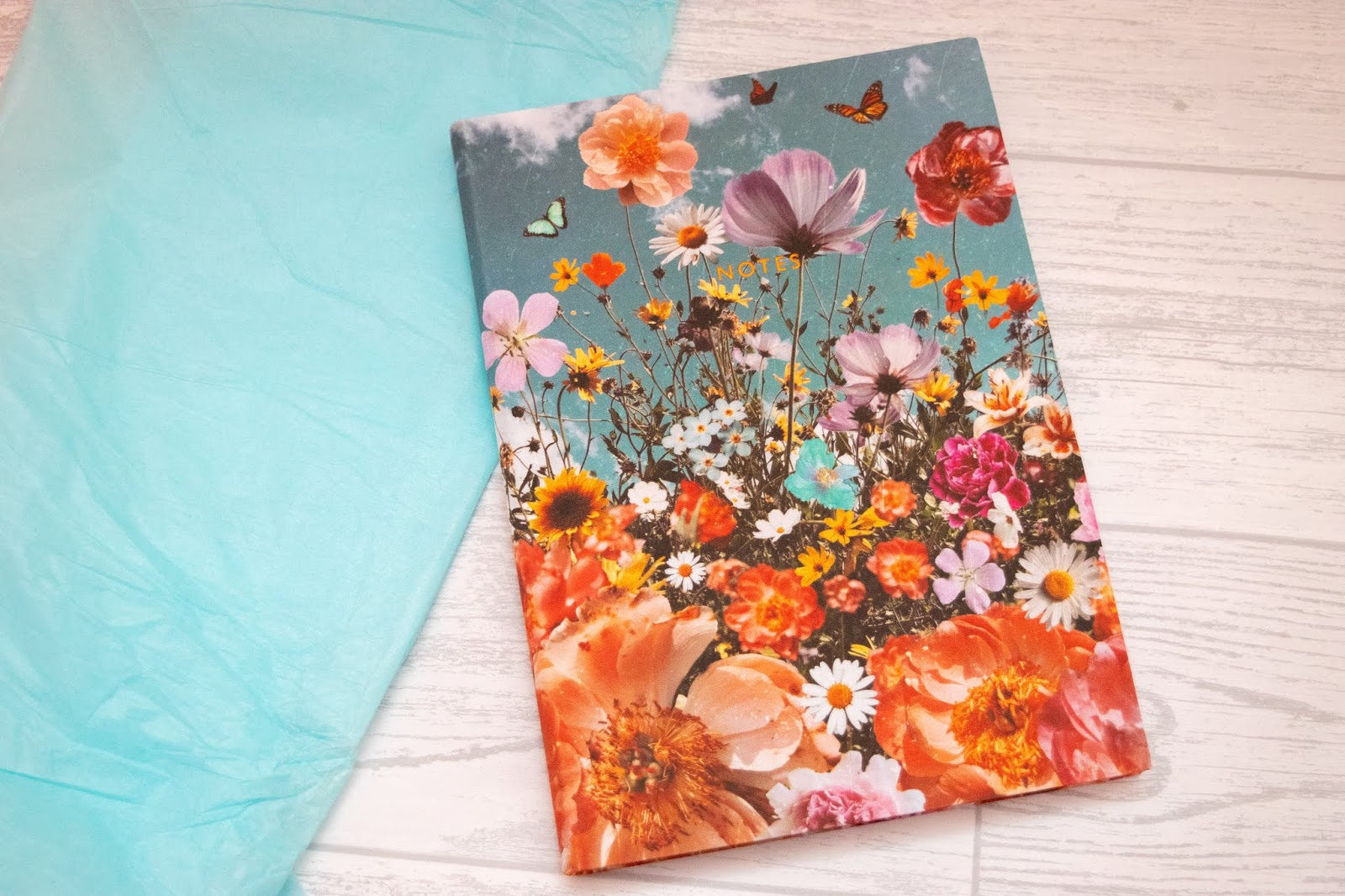 A blue fabric notebook with colourful wildflowers all over and notes written in gold foiling and capital letters in the centre.