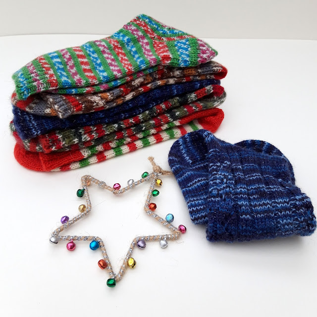 A stack of multi-coloured socks in the WYS Christmas yarns.  To the fore is a star decoration with tiny coloured bells on it, and to the right is a knitted sock in Silent Night sparkly yarn, all on a white background