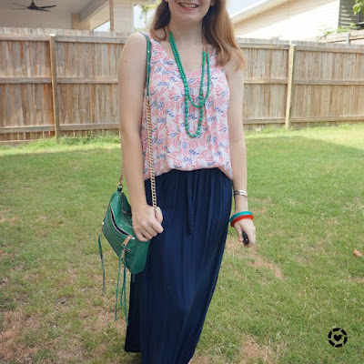 subtle red and green Christmas shopping outfit with navy maxi skirt and green bag   awayfromblue Instagram