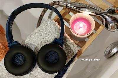 Kopfhörer mit Kerze und Handtuch