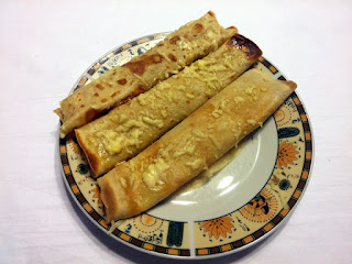 Zapiekane naleśniki z porem i szynką podane na talerzu. Idealne na obiad lub kolację.