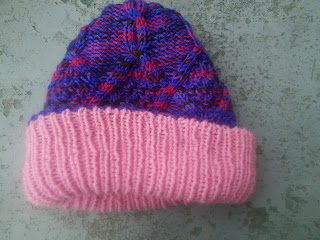 A knit purple hat with cables, with a folded up pale pink brim.