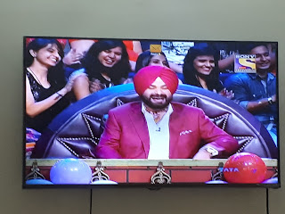 """In the blog """"The Kapil Sharma Show Is Well Past It's Expiry Date, rottenmangoman tries to analyse whether a show can be sustained on old outdated gimmicks. In this image of Navjyot Singh Sidhu always laughing forcefully with 4-5 pretty looking girls sitting behind him."""