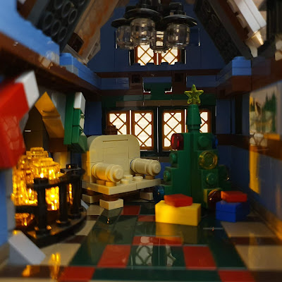 A room recreated in LEGO, with a lit up fireplace, Christmas tree with presents and an empty chair.