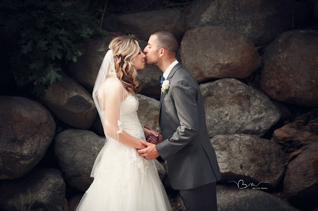 bride and groom on by stone wall at Noah's Event Venue in Auburn Hills Michigan
