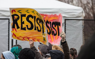 "People at demonstration holding up two hand-lettered signs that read ""RESIST"""