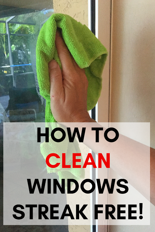 How to clean windows streak free. Hand with green rag cleaning window