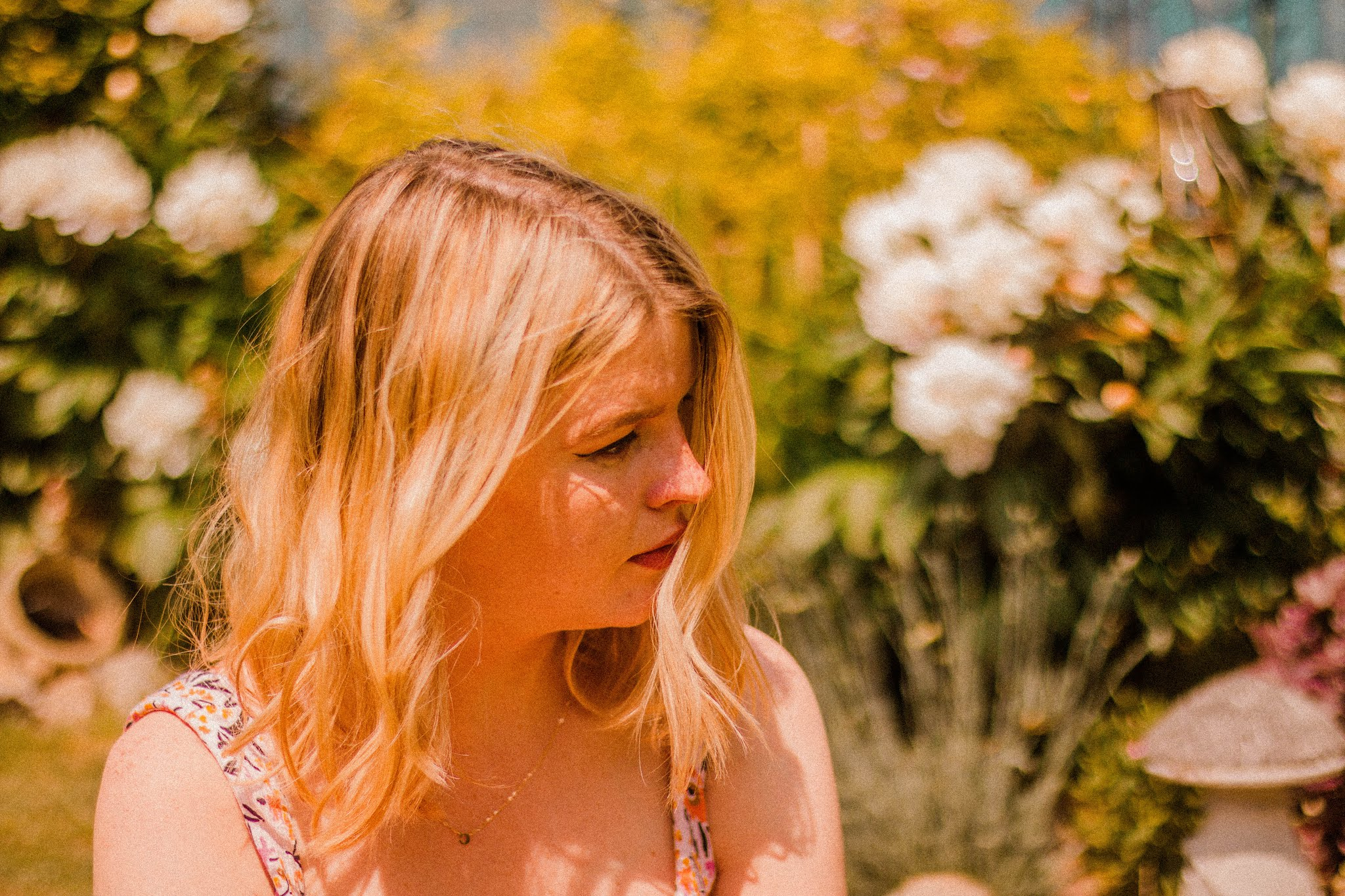 blonde girl in garden wearing floral playsuit - summer bucket list