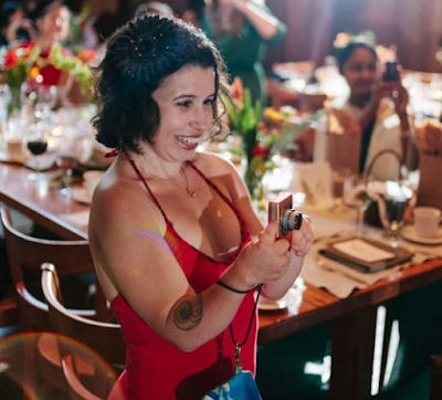Small Latinx white woman in beight red dress, short dark hair, smiling, and taking photos of a crowd at a party.
