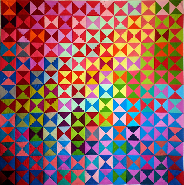 A rainbow of colorful fabrics makes this simple pattern into a stunning quilt.