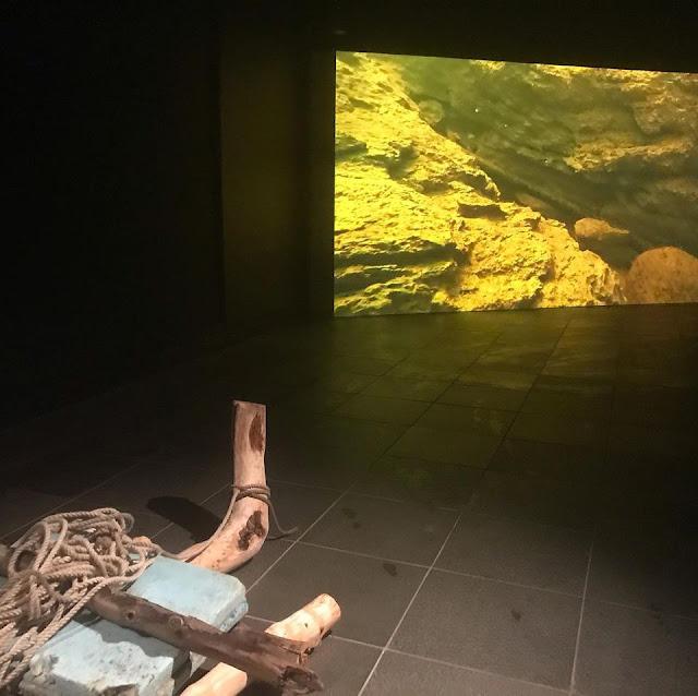 Vedenalaista savikanjonia videolla seinälle heijastettuna, etualalla ajopuista tehty taideteos lautasta