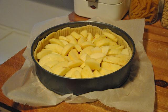 Apfelstücke auf dem Mürbteigboden verteilen