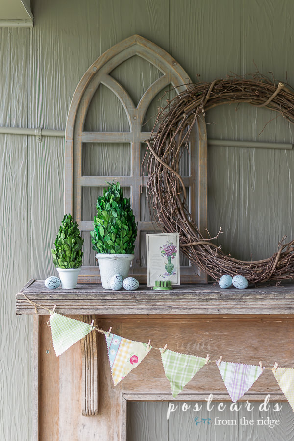 preserved boxwood topiaries and grapevine wreath on rustic mantel