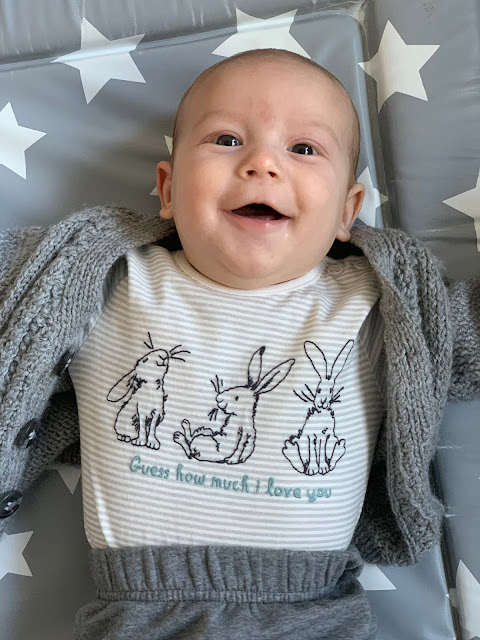 Baby Boy smiling up from the changing mat at 3 months old, wearing grey