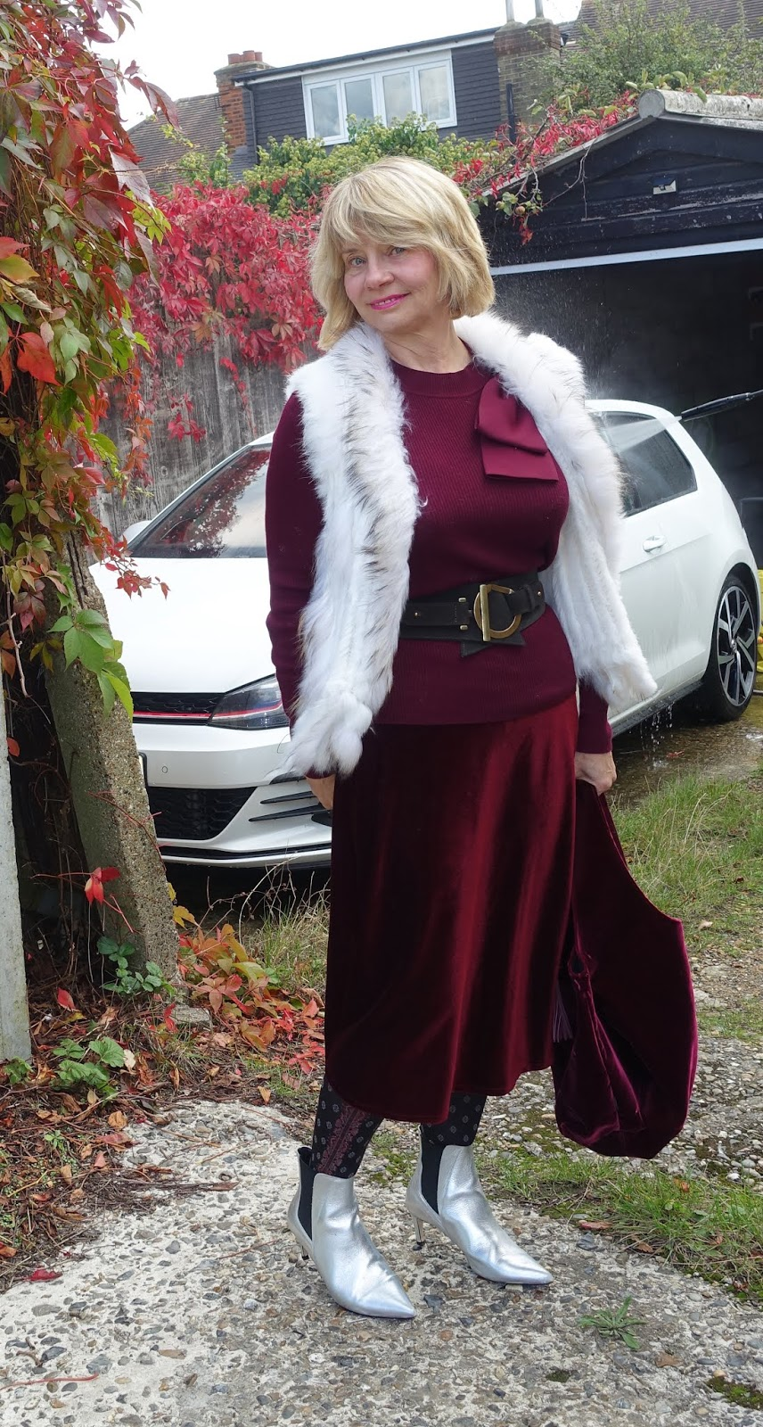 Framed by a Virginia creeper Is This Mutton blogger Gail Hanlon is wearinbg a monochrome burgundy outfit with a white fur gilet and patterned tights