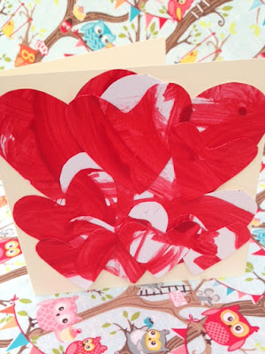 Handmade card decorated with painted heart shapes cut out