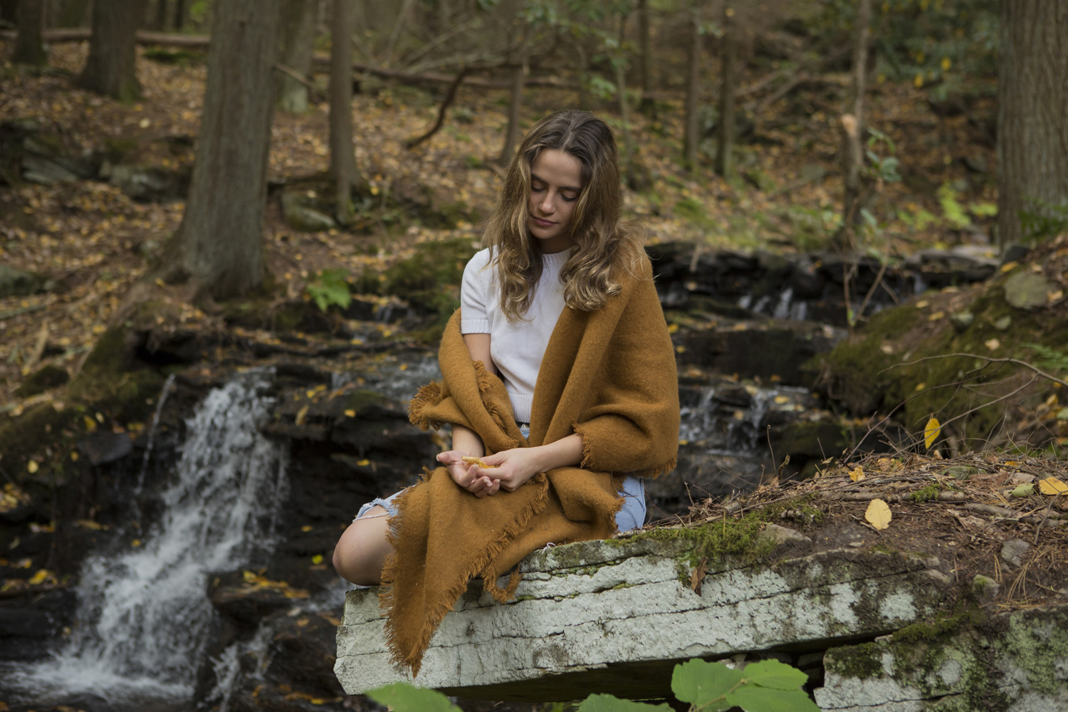 a woman wearing fall outfit, sitting in the forest