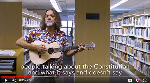 snapshot from video, featuring Chris playing guitar.  Closed caption: People talking about the Constittuion and what it says and doesn't say.