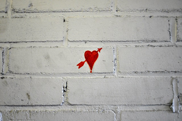 hand-drawn red heart with arrow on white brick wall