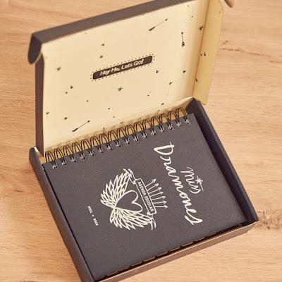"""Agenda de Lucia Be. En la portada negra aparece la frase """"Miss Dramones"""". La agenda está metida en una caja que pone """"Hey, oh, lets go"""""""