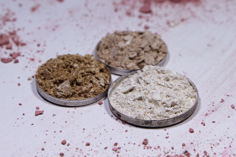 a close-up studio photo of three crushed eyeshadows
