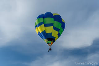 Cramer Imaging's fine art photograph of one single-passenger hot air balloon taking flight in Panguitch Utah with a blue partly cloudy sky