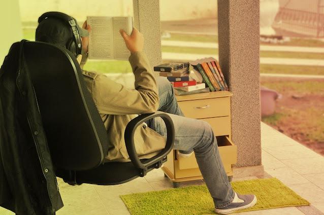 Pessoa lendo e ouvindo música no headset ao mesmo tempo