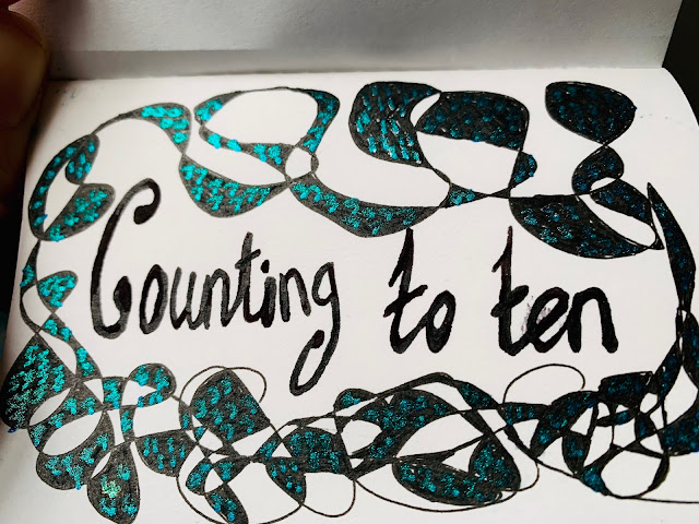 Counting to ten surrounded by a pattern with numbers written on in a metallic pen like fish scales