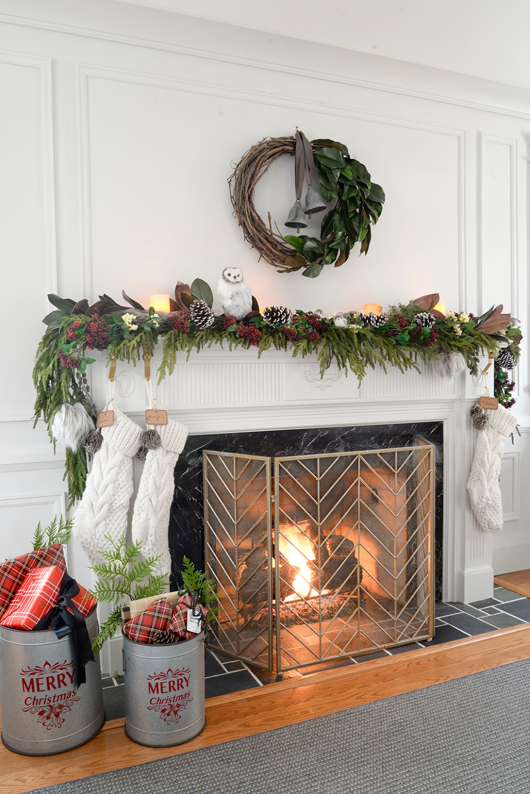 a faux christmas fireplace mantel garland with red seeded eucalyptus, a cedar garland and magnolia leaves. A galvanized bucket holding christmas gifts