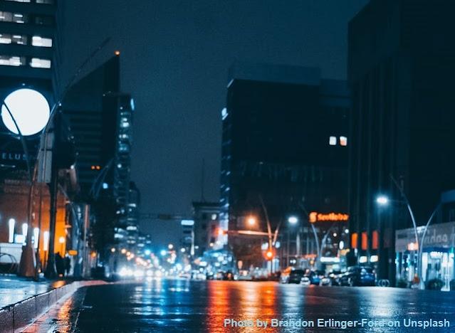Cena urbana noturna, com reflexos de luzes no asfalto molhado e luzes de veículos ao fundo