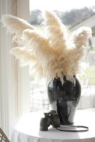 WHITE PAMPAS GRASS in a black pot with 2 ceramic owls sitting next to it.