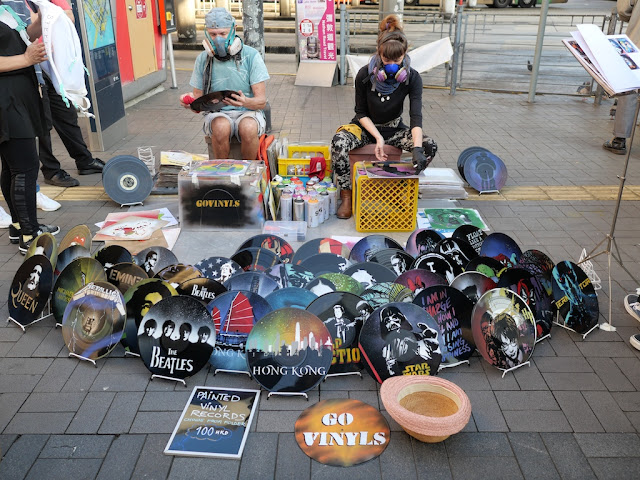 two artists wearing respiratory masks spray painting vinyl records