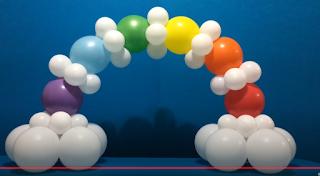 Kleiner Ballonbogen aus regenbogenfarbenen Luftballons zur Tischdekoration.
