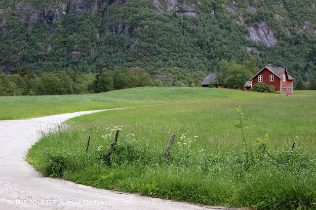 A curved gravel path that leads to a red farm house in front of towering cliffs in Hæreid in Eidfjord in Norway