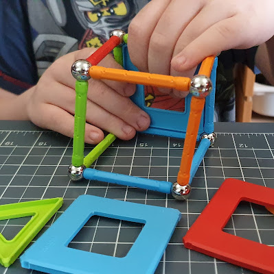 Boys hands in view making an open sided cube shape with Geomag