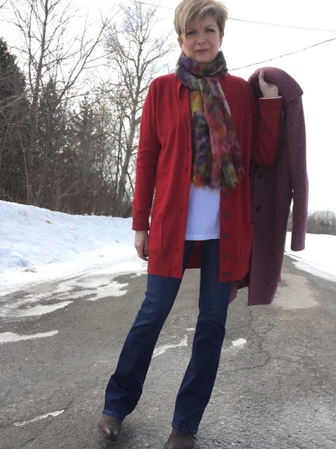 woman in red sweater and jeans holding a tweed coat.