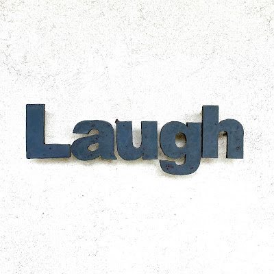 The word laugh in metal on a white wall