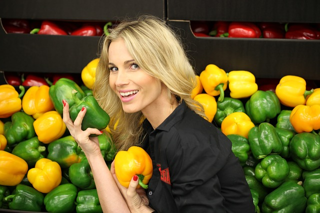 Woman Holding Green and Yellow Sweet Peppers