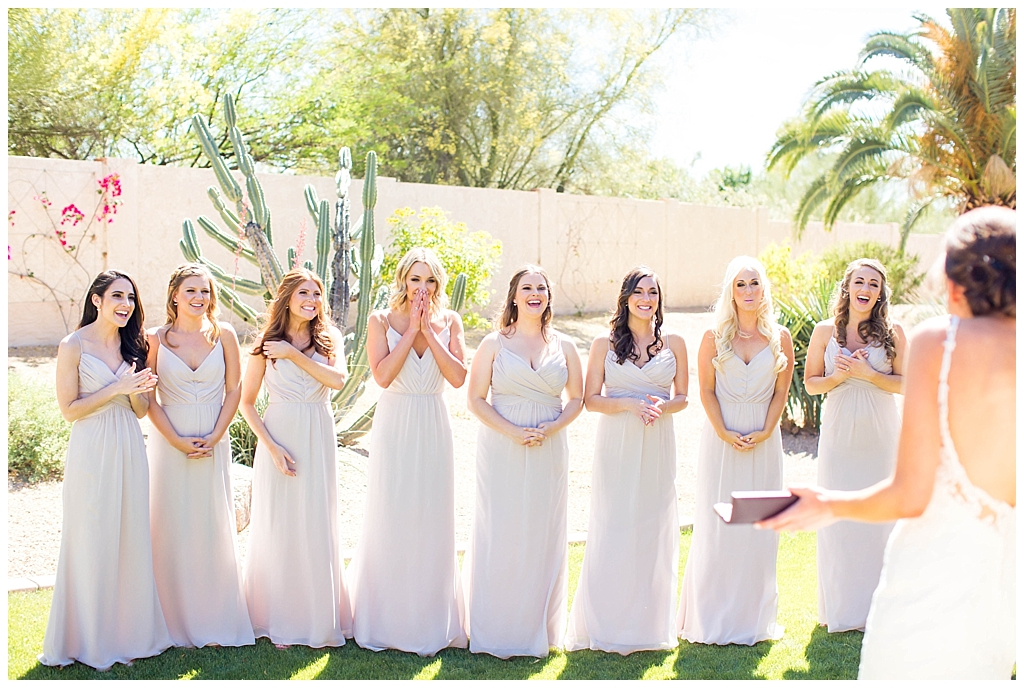 bridesmaids in blush dresses seeing bride for the first time