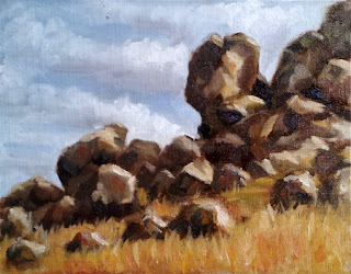 Oil painting of large rocks and boulders with dry grass.