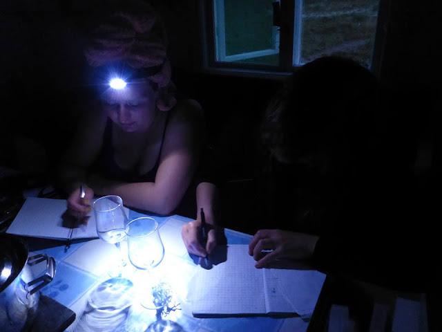 Kaksi henkeä tekee töitä otsalampun valossa pöydän ääressä pimeässä huoneessa