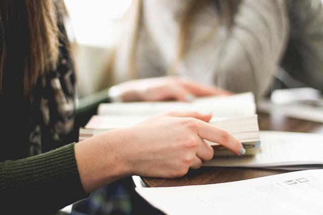 Mulher lendo um livro sentada à mesa