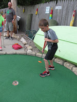boy putting on mini golf green