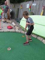 boy putting on mini golf green