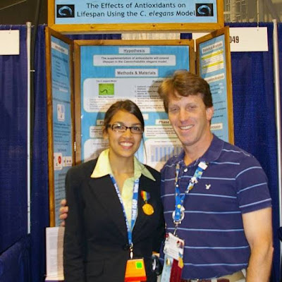 Alexandria Ocasio-Cortez with her Intel 2007 science fair project and Yorktown high school teacher Michael Bluegrass.