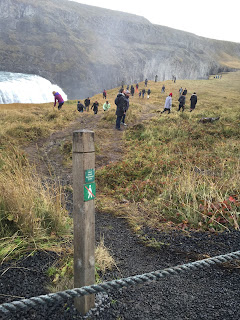 Tourists behaving badly at Gullfoss falls - they ignore the sign and go off the path