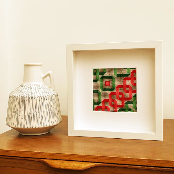 Interlocking squares needlepoint in green and coral framed picture