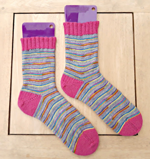 Image shows a pair of socks on purple sock blockers lying on a pale wooden table.  The socks have pink cuffs, heels and toes, and the leg and foot of each sock is knitted in grey and rainbow striped yarn