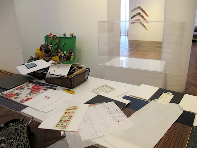 Table in a gallery in front of an empty display case. On the table are various cardboard walls and floors of miniature scenes.