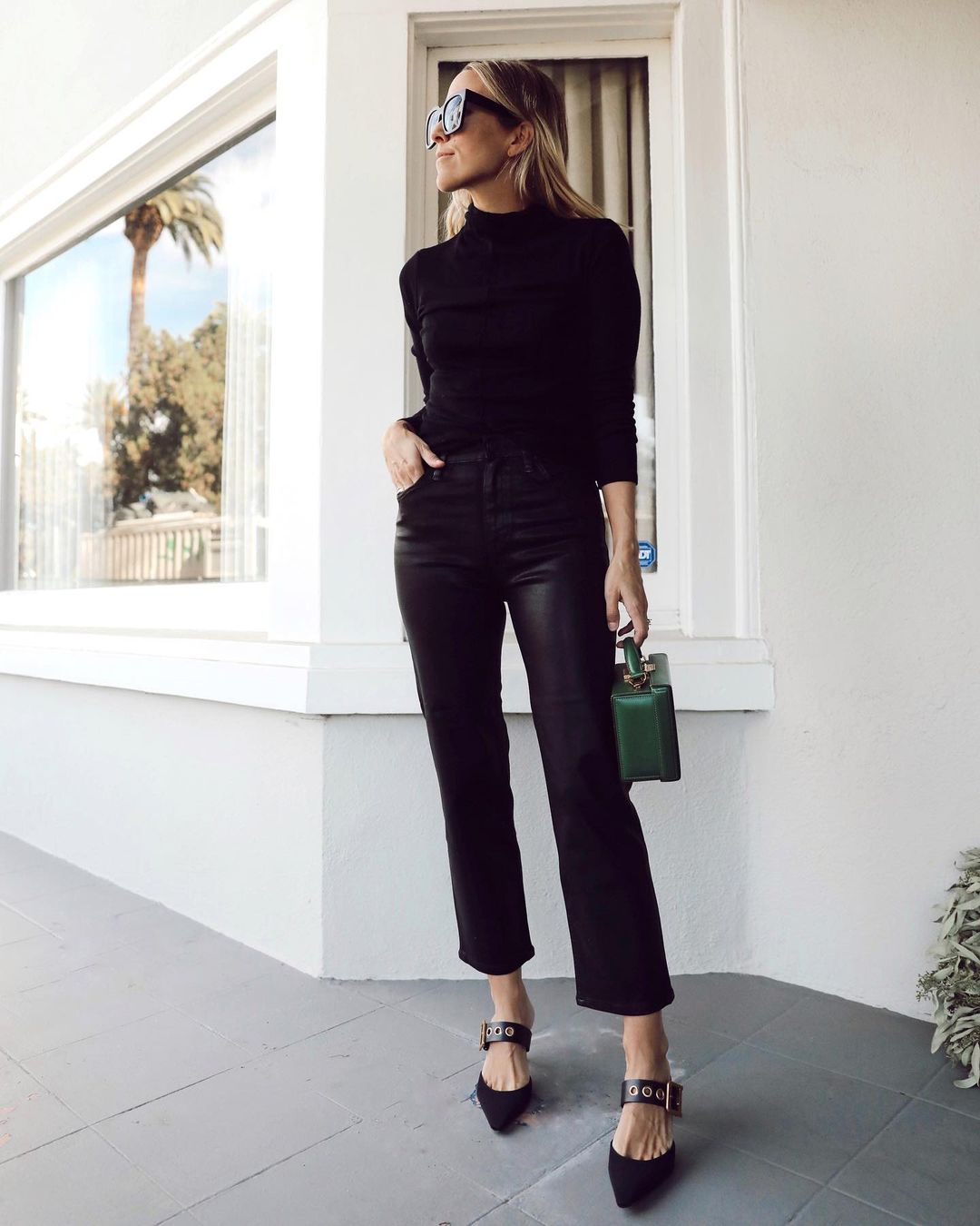 Instagram star Jacey Duprie in an all-black outfit idea with turtleneck faux leather jeans, and pointed-toe mule heels